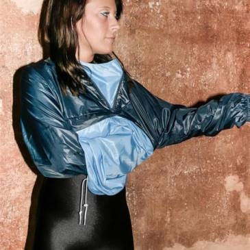 Black spandex catsuit and shiny nylon Adidas windbreaker